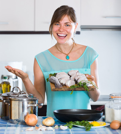 saltwater fish: Happy female frying saltwater fish slices at home Stock Photo