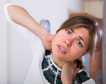 Tired brunette young girl suffering of heavy pain in neck
