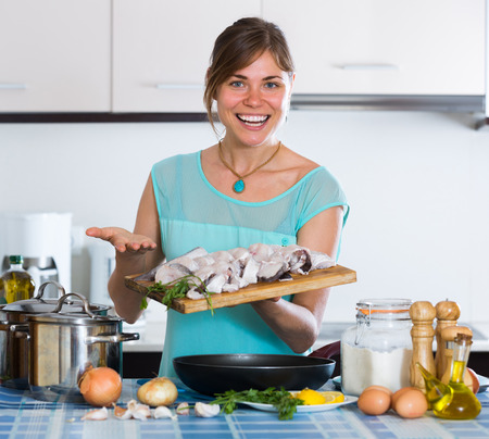 saltwater fish: Happy housewife frying saltwater fish slices at home