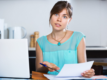 Sad young woman reading banking statement