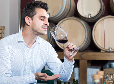 look latino: positive latino man having wine tasting in cellar with woods