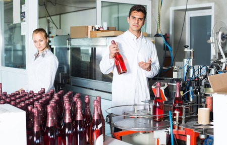 technic: portrait of man and woman in white robes working on wine production on manufactory. Focus on man