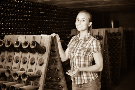 aging woman: Young smiling positive woman winery employee standing in aging section with bottles on winery manufactory Stock Photo