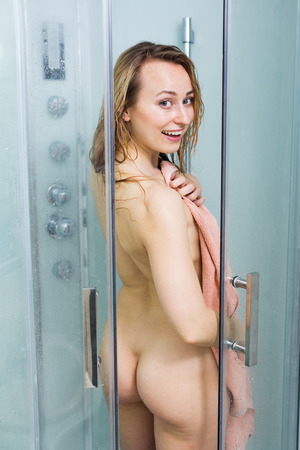 naked youth: portrait of sexy naked woman covering herself with towel in glass shower unit doors