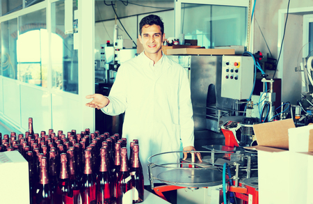 white robe: portrait of young man in white robe working on wine production on manufactory Stock Photo