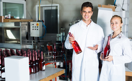 wine register: Two colleagues holding newly produced bottles of wine on winery manufactory Stock Photo