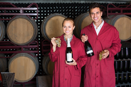 big cork: Two cheerful winery employees in uniform holding bottles of wine in aging section in cellar