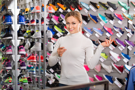 promoting: Smiling girl promoting shoes in the sport boutique