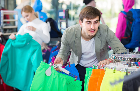 russian man: happy russian man gladly choosing a sport shorts in the shop Stock Photo