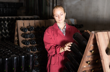 aging woman: Laughing woman winery employee in coat working in aging section with bottle racks in cellar