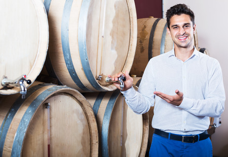 look latino: Glad man winery owner standing in shop with wine woods Stock Photo