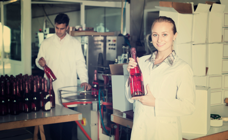 Two cheerful colleagues holding newly produced bottles of wine on winery manufactory