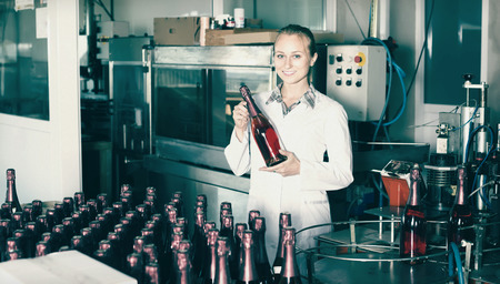 wine register: smiling woman holding newly produced bottles of wine on winery manufactory Stock Photo