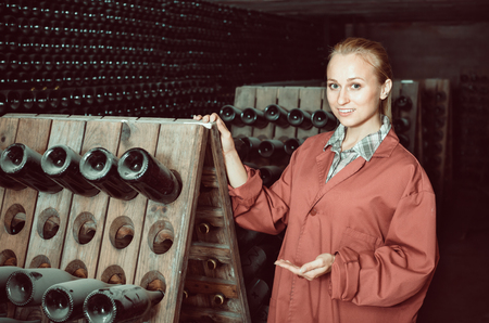 aging american: Happy woman in uniform working with bottle storage racks in winery cellar Stock Photo