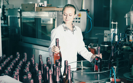 technic: young positive woman holding newly produced bottles of wine on winery manufactory