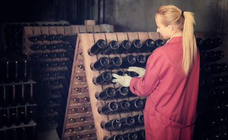 aging woman: Happy woman winery employee in coat working in aging section with bottle racks in cellar