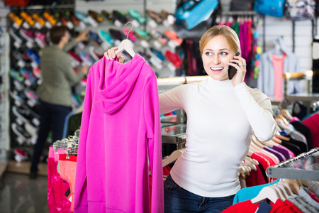 gladly: spanish girl gladly speaking on the phone and choosing a sport jacket Stock Photo
