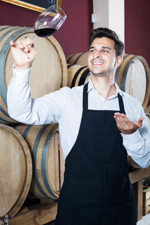 Smiling man seller in apron holding glass of red wine in shop with woods