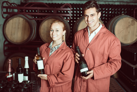aging american: Two happy winery employees in uniform holding bottles of wine in aging section in cellar