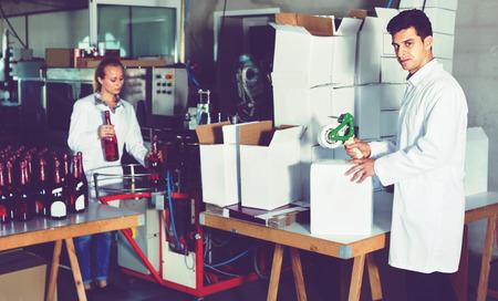 diligente: hombre diligente amigable contenta en el abrigo de pie en la sección de embalaje en la fábrica de elaboración del vino