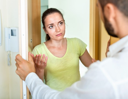 irritated: Young irritated couple  quarreling at the door