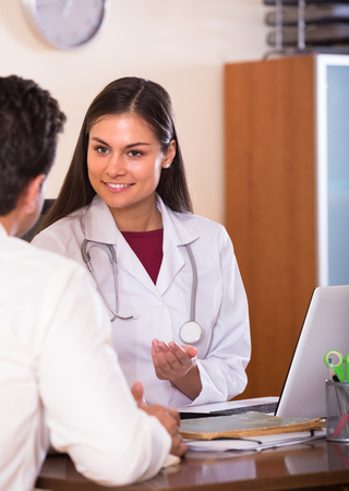 Portrait of patient and smiling female therapeutist at desk in modern clinic Stock Photo