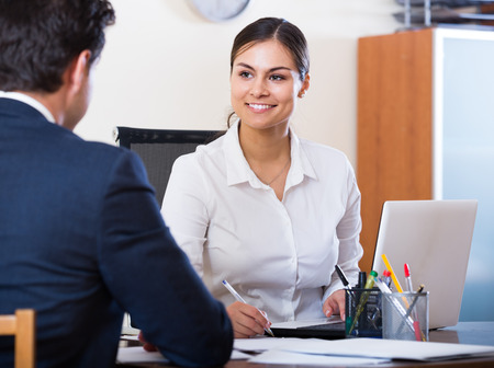 conduction: Banking european agent listening to customer and smiling in agency