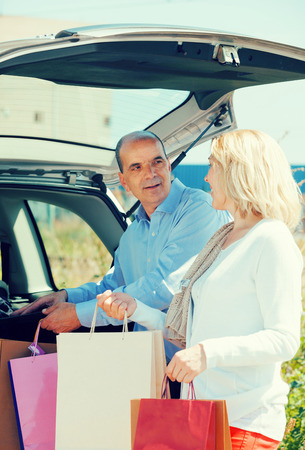 novelties: Smiling senior mature couple staying near opened boot with purchases