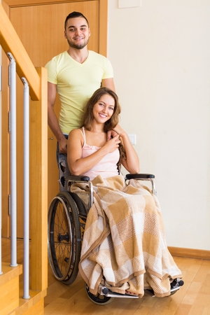 coming home: Young positive man and his pretty disabled wife in wheelchair coming home. Focus on woman Stock Photo