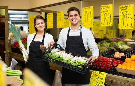 positive market workers with assortment of apples, prices on Spanish