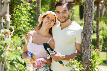 floriculturist: Young happy couple is engaged in gardening