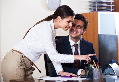 Manager and smiling russian assistant brainstorming in office