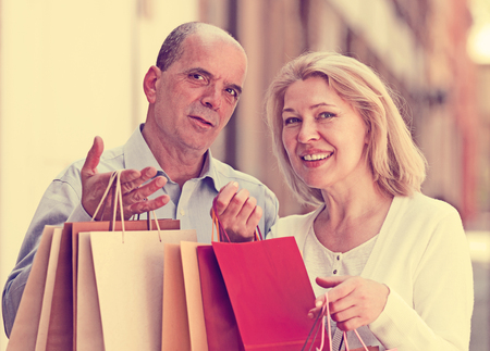 Lovers senior with mature woman having shopping tour in city and smiling