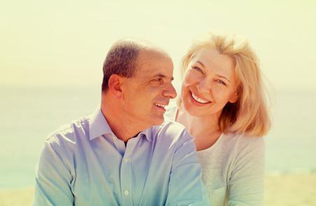 Sonriendo pareja de ancianos luna de miel en la orilla del mar en la estación cálida