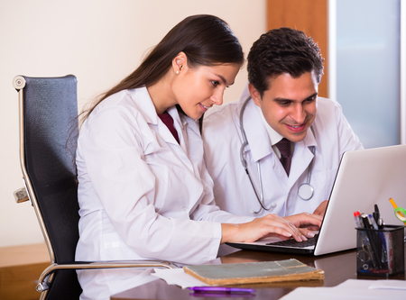 physiotherapists: Young intern asking advice from medical tutor at clinic reception. Focus on woman Stock Photo