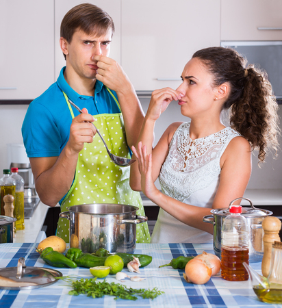 foul: Surprised male and female feeling foul smell of food from casserole Stock Photo
