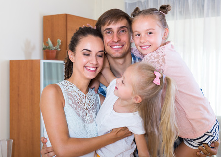 Portrait of happy smiling young parents with two cute little daughters at home