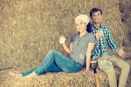 Young cheerful man and woman sitting together in the hay and land drinking fresh milk