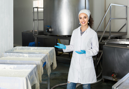 lab coats: Portrait of young woman dressed in lab coats is looking happy on the factory