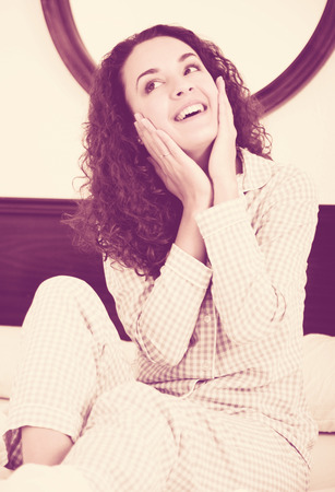 Portrait of curly haired woman doing face massage in bed Stock Photo