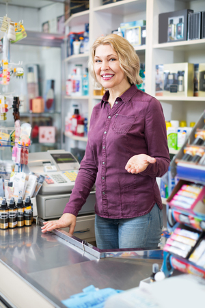 Friendly mature female seller at the counter in beauty store