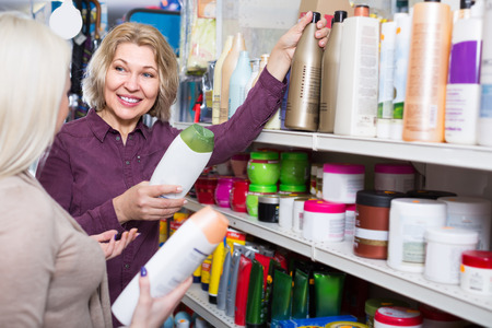 Happy mature woman and her adult daughter choosing shampoo in supermarket
