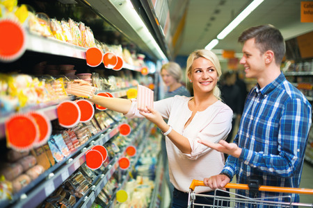 provision: Positive smiling family couple choosing chilled sausages in shop Stock Photo