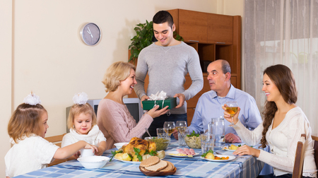 relatives: Smiling adult family member receiving present from relatives at table