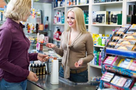 cliente sonriente positiva en la tienda de pagar en efectivo escritorio registro Foto de archivo