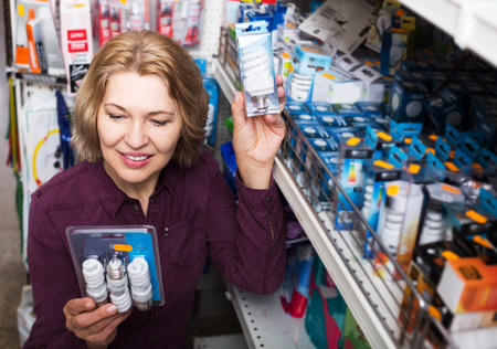 Aged woman chooses bulbs in hardware store