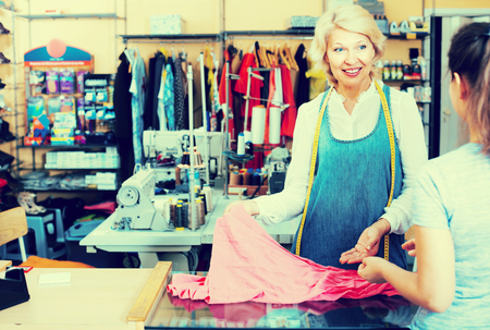 customer tailor: smiling mature woman tailor bringing clothing from customer in sewing studio Stock Photo