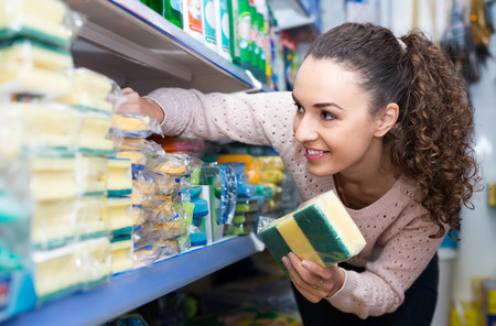 Positive young housewife buying sponge for cleaning in shopping mall