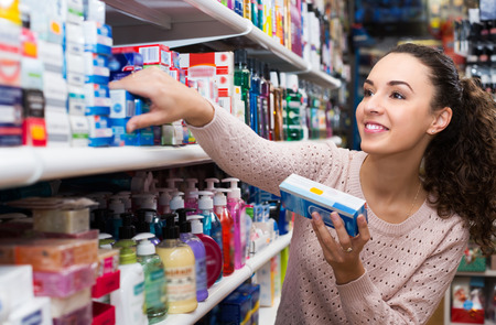 Smiling female customer buying toothpaste for sensitive teeth in store Фото со стока