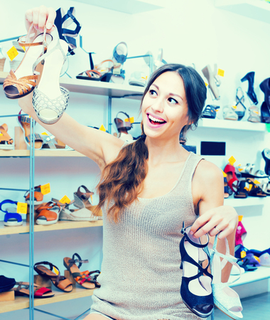 chosen: positive young girl standing in store with many chosen shoes in hands